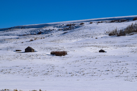 Snow covered Colorado hillside with log cabin in Winter