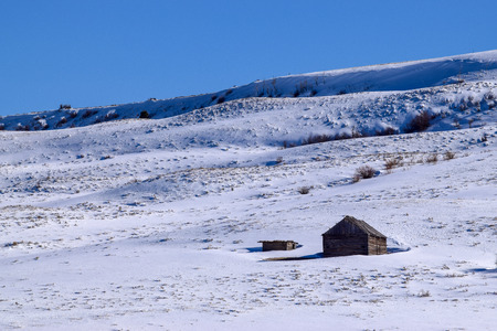 Snow covered Colorado hillside with log cabin
