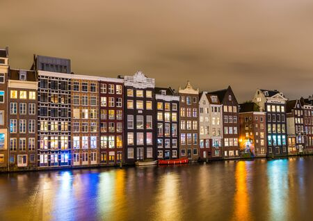 Facades on the Damrak at night in Amsterdam in the Netherlands Stock Photo