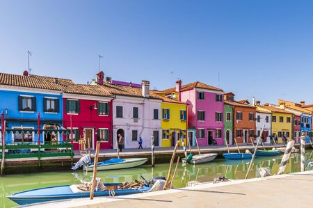 A canal and its colorful facades on the Isle of Burano in Venice in Veneto, Italy