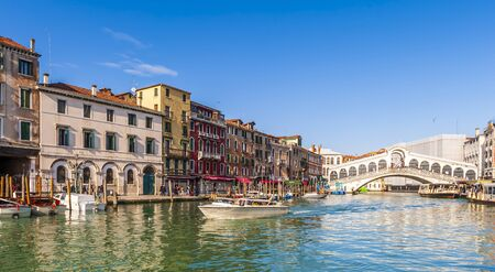 The Grand Canal and its typical facades and the Rialto bridge in the background in Venice in Veneto, Italy