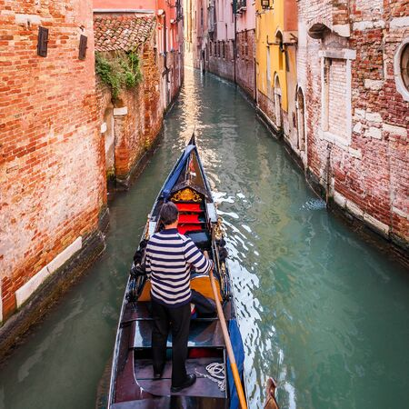 Canal and its typical facades and gondolas in Venice in Veneto, Italy