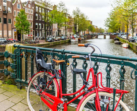 Red bicycle on a bridge in Amsterdam in Holland in the Netherlands