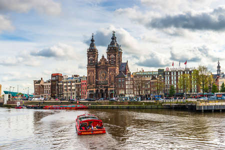 View of St. Nicholas Church main catholic church in the city, and boat traffic on the Amstel in Amsterdam in Holland, Netherlands 版權商用圖片