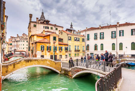 Typical place with successions of bridges and tourists in Venice in Veneto, Italy