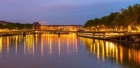 Panorama of the Saone docks illuminated at dusk, in Lyon, in the Rhone, France