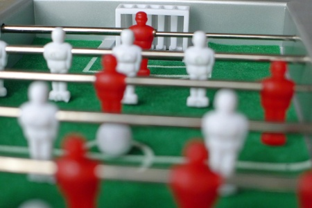 kickoff: Close-up of table football game with red and white figures, shallow focus, ball ready for kick-off