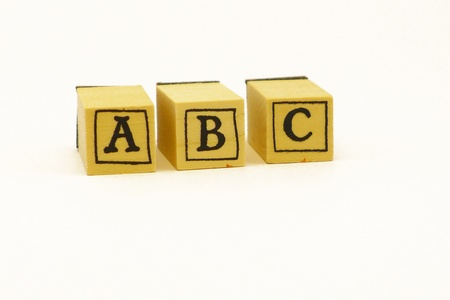 alphabetical order: Three wooden cubes, with the letters A, B and C visible in alphabetical order, isolated on white background