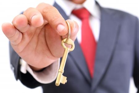 trade secret: businessman showing the golden key to success