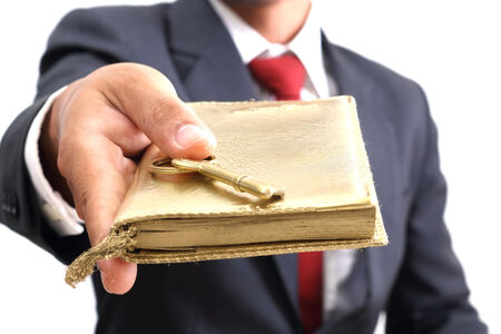 businessman showing the golden book and key to success photo