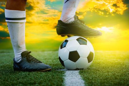 kickoff: feet of football player tread on soccer ball for kick-off