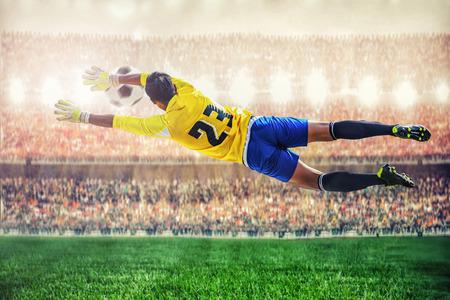 portero de futbol: soccer goalkeeper flying to catches the ball in the stadium
