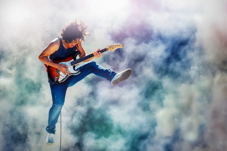 star: rock star guitarist jumping and playing electric guitar on the stage