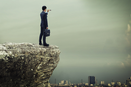 monocular: businessman standing on the top of mountain and searching the opportunity concept by monocular Stock Photo