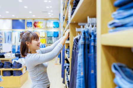or spree: Smiling asian girl shopper choosing new jeans at store