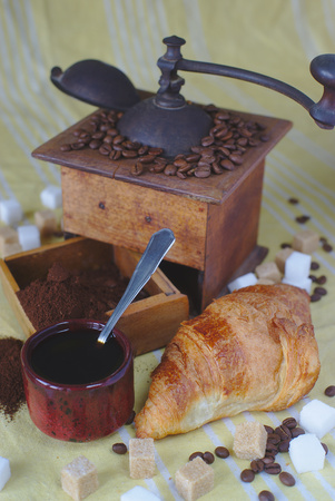 old coffee grinder, cup, spoon and cubes of brown and white sugar. Croissant Stok Fotoğraf