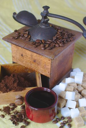 old coffee grinder, cup and brown and white sugar cubes Stock Photo