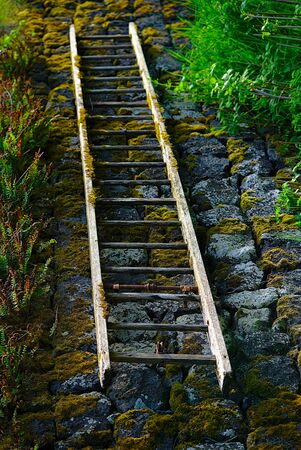 old wooden ladder worm-eaten on a stone wall in perspective Banco de Imagens
