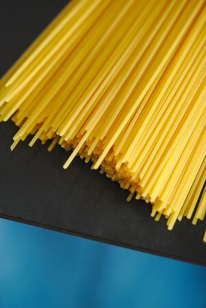 Spaghetti loose on a black table edge and blue background