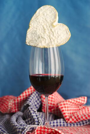 Composition with Neufchatel, Norman cheese (A.O.P.) and glass of wine, on a blue background.