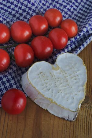 Neufchatel cheese (A.O.P. Normande) and a cluster of cherry tomatoes. Rustic background
