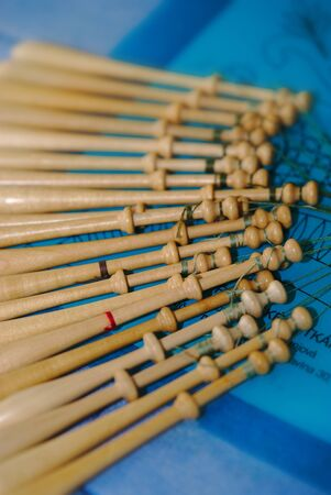 bobbins of lacemaker in wood on blue background