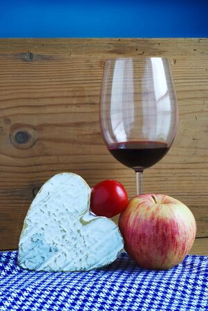 still life with a Norman cheese Neufchatel (A.O.P.) a cherry tomato, a glass of red wine and an apple on wooden background and blue fabrics 写真素材 - 126983737