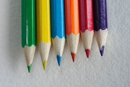 six rainbow colored pencils on a white paper