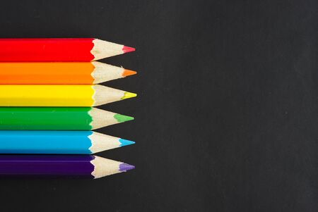 six rainbow colored pencils on a black sheet with space for text