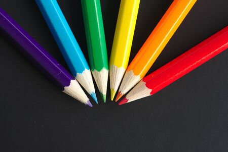 six rainbow colored pencils on a black sheet with space for text 写真素材 - 128655056