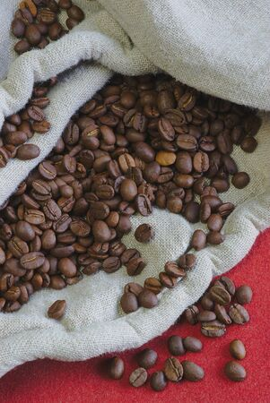 coffee beans and canvas bag on red background