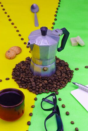 objects evoking coffee break with small traditional Italian coffee maker on green and yellow background. Coffee beans.
