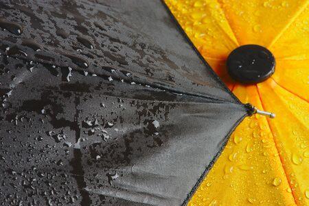 wet yellow and black umbrella cloth, close up Banco de Imagens
