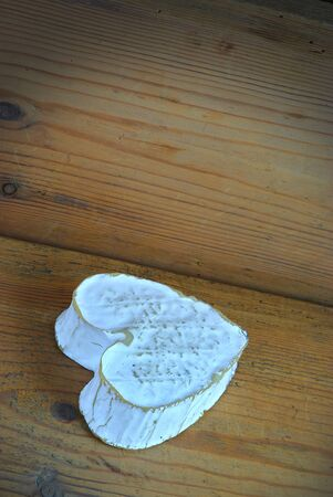 Neufchatel, Normand cheese in the shape of a heart (A.O.P.). From the Neufchatel-en-Bray region, on a wooden background