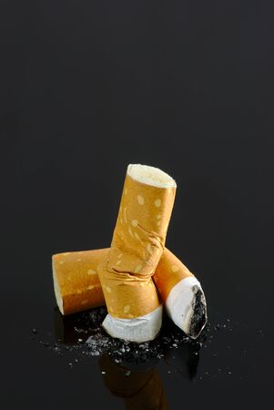 Crushed cigarette butts isolated on black background Stockfoto