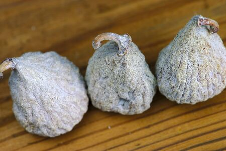 three dried figs close-up on a wooden board