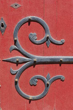 detail of wrought iron ornamentation, of a red door