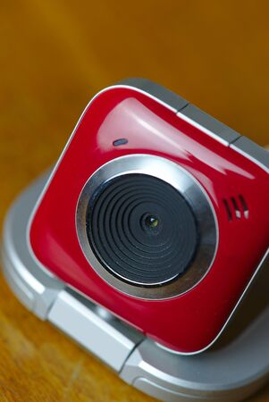 red and white webcam close up on wooden background