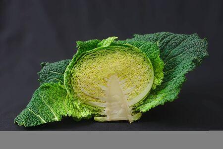 half green cabbage cut on black background