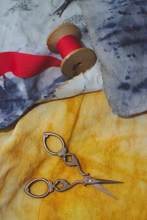 several pairs of old sewing scissors and a spool of red ribbon