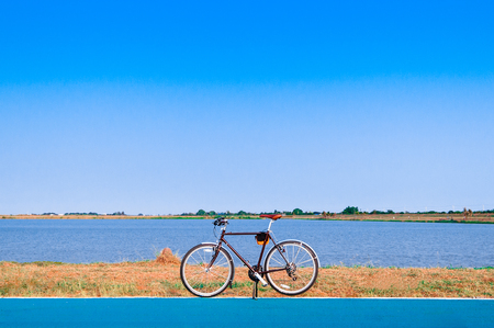 A Bike by the lake with clear blue summer sky.