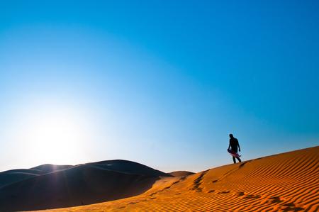 Eén man staat alleen in de Al Wathba-woestijn. Abu Dhabi.