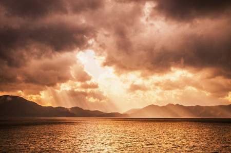 Sunset sky before storm with divine ligth at lake Tazawa, Semboku, Akita, Japan. 写真素材
