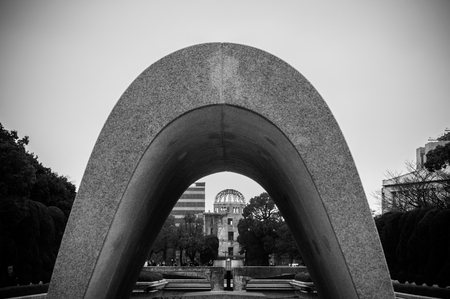 A concrete, saddle-shaped monument that covers a cenotaph holding the names of all of the people killed by the bomb. The monument is aligned to frame the Peace Flame and the A-Bomb Dome. Photo was shot on Dec 21, 2015.