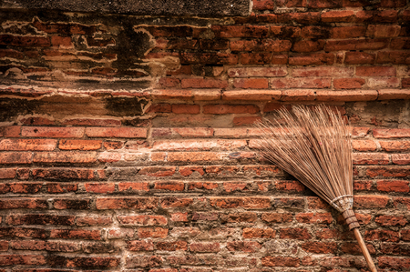 Vintage style broom put against the old brick wall. Stock Photo