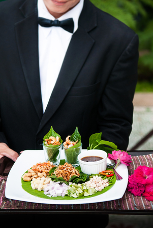 Miang Kham is Thai appetizer dish. Traditional snack from Thailand and Laos. Mostly use fresh Piper sarmentosum or Erythrina fusca leaves that are filled with roasted coconut and other small pieces of ingredients and sweet sauce. Stock Photo
