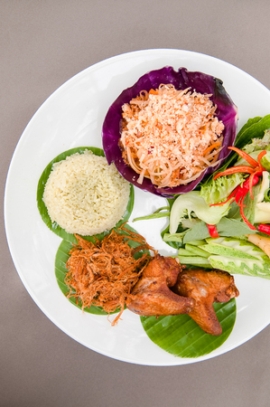 Thai traditional dish, Rice cook with coconut milk eat with Som Tum (Papaya Salad), shredded sweetened pork and fried chickens.