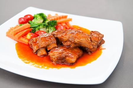 Pot roasted por ribs with tomato base sauce.