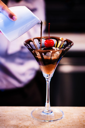 Pouring Dark Chocolate sauce onto Chocolate Ice cream with cherry on top