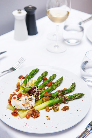 Grilled green asparagus and poached egg with balsamic dressing and tomato